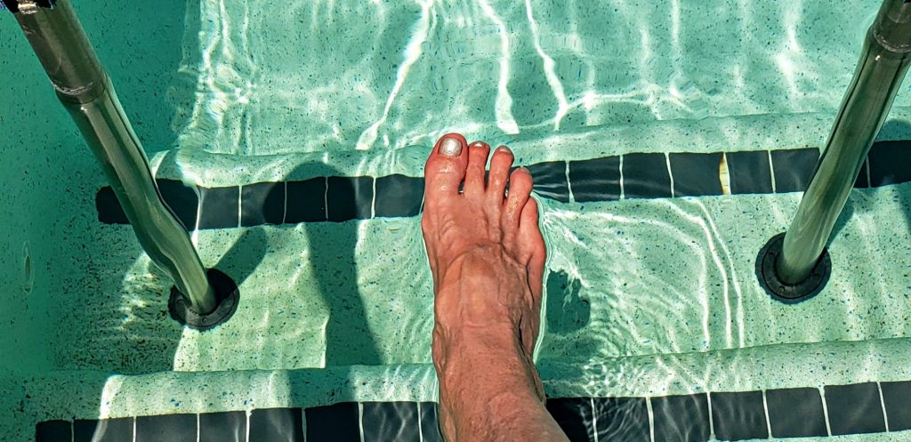 Woman's toe points to aquamarine water in clear swimming pool