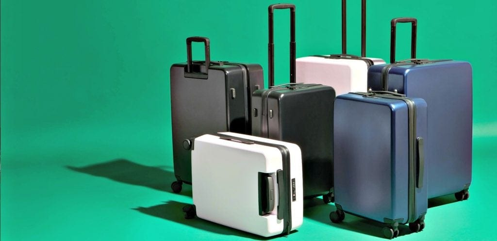 six suitcases - the best lightweight luggage for international travel - shown against green background with dramatic shadowsing
