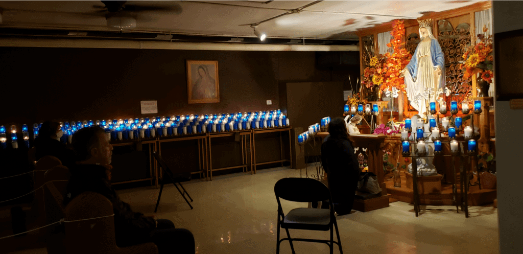 Dark, low ceiling room is lined with candles, some in blue glass while people pray in front of a statue of Mary