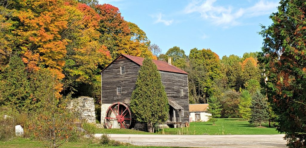 Weathered vintage 2.5 story mill calle historic Rock Mill thick forest that is changing to fall colors on Wisc Way pilgrimage
