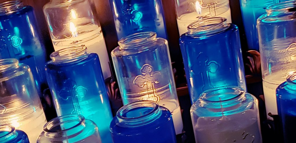 close up of candles in blue and clear jars at National Shrine of Our Lady of Good Help