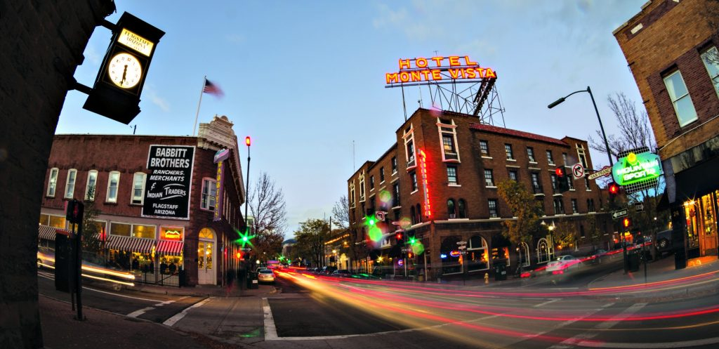 wide angle view of downtown Flagstaff at dusk with neon lights stop Hotel Monte V an Babbitt Trading Co - best things to do in Flagstaff Arizona
