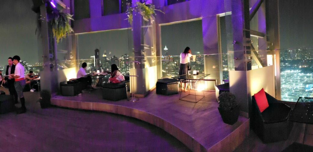 woman stands at glass wall overlooking open air city scape at night - purple lights set mood at this posh rooftop bar in Bangkok