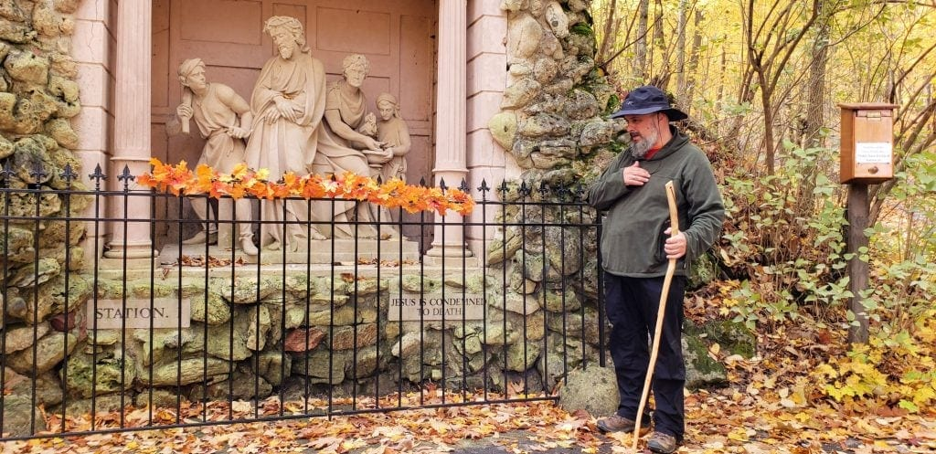 Man with black hat and wooden walking stick taps his heart in front of one of the Stations of the Cross at Holy Hill Church Wisconsin