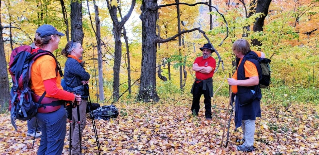 three pilgrims stand facing man in red shirt and black hat - surrounded my trees in fall colors - leaves on ground