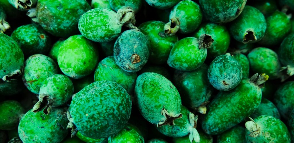 Green fruit packed into a market bin - close up of the exotic fruit