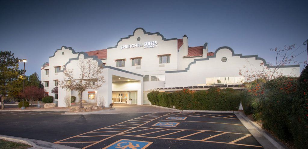 Exterior of 3-story hotel in Prescott AZ: white, adobe-style walls with Santa Fe-style trim and red tile roof. Clean facade and parking lot show this is one of the top lodging in Prescott