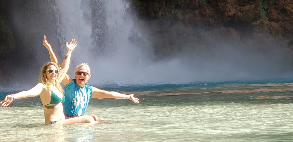 Charlotte and Stacey in water with Havasu Falls behind