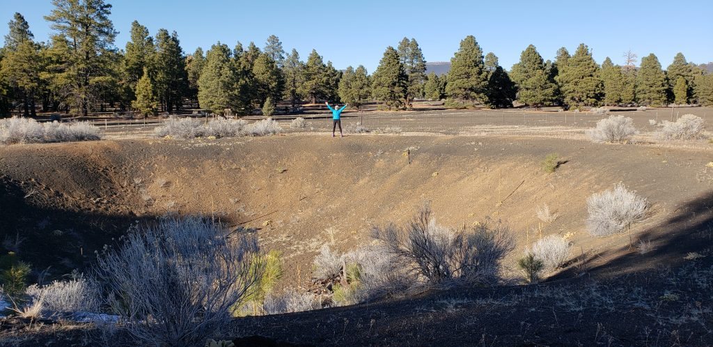 small figure raises arms in applause on far side of Flagstaff cinder crater