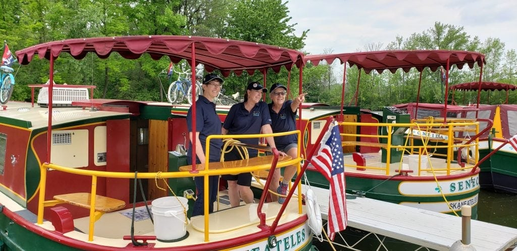 Three women stand at stern Erie Canal rental boat