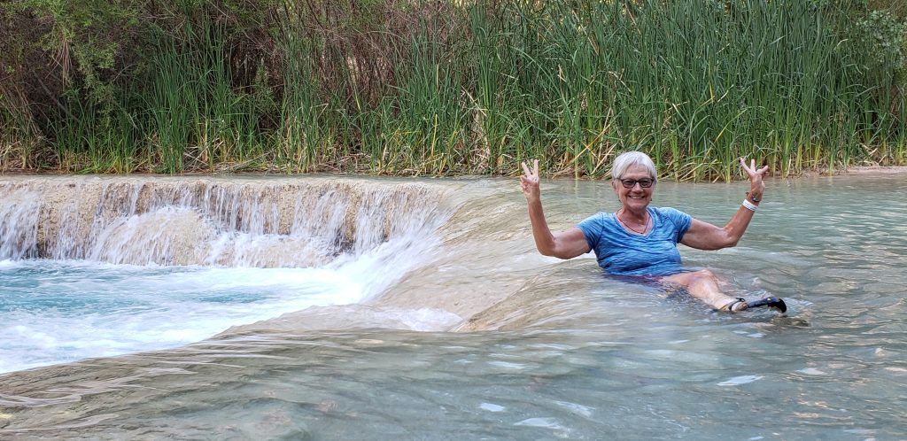 Author Unstoppable Stacey sits in 70F blue-green waters of Havasu Creek