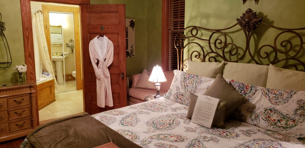 King bed be-decked in colorful bed linens, robe hangs on door at Asheville B&B near Biltmore