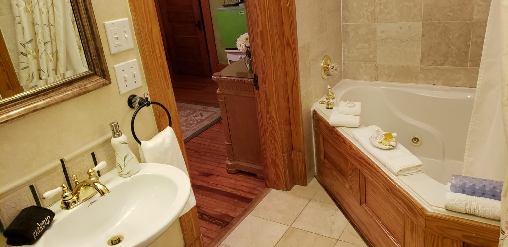 Bathroom with 12-inch tile floors, Jacuzzi bathtub for two and sink at Cumberland Falls Bed and Breakfast