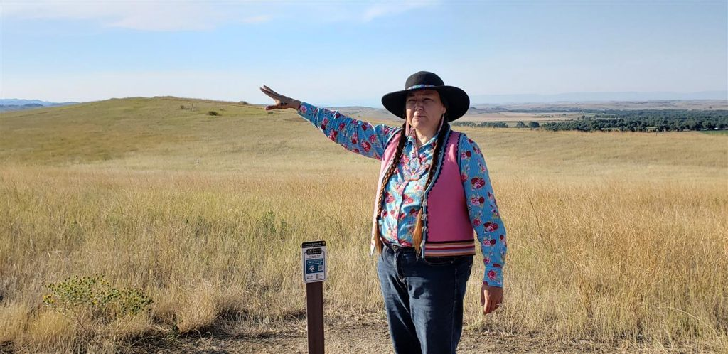 Native woman in authentic wild west garb and braids points out over the prairie grasses of Little Bighorn Battlefield.