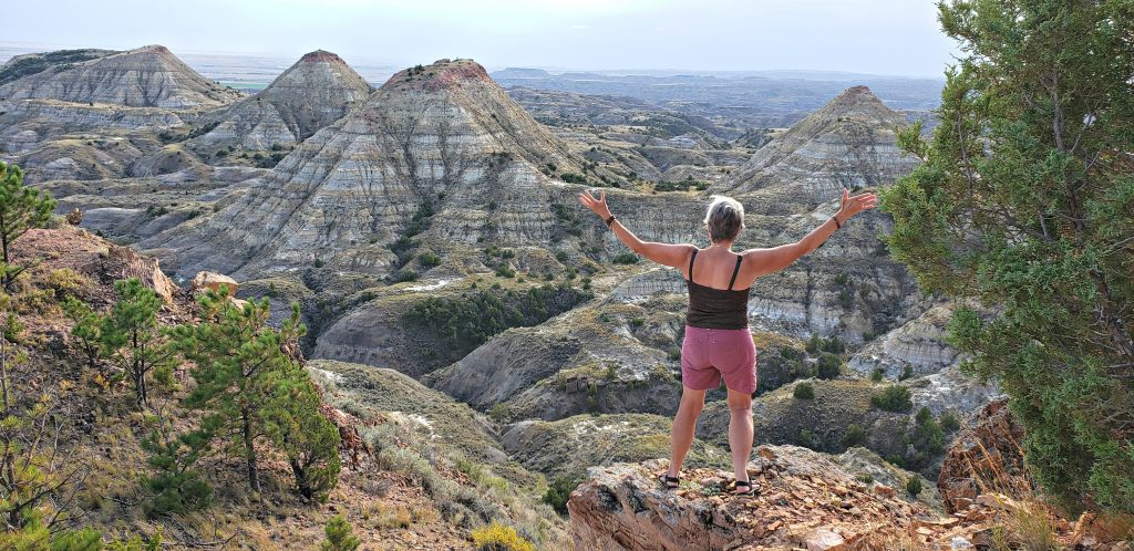Author Stacey Wittig stands with back to camera and arms outstretched overlooking Terry Badlands. Dark clouds in background