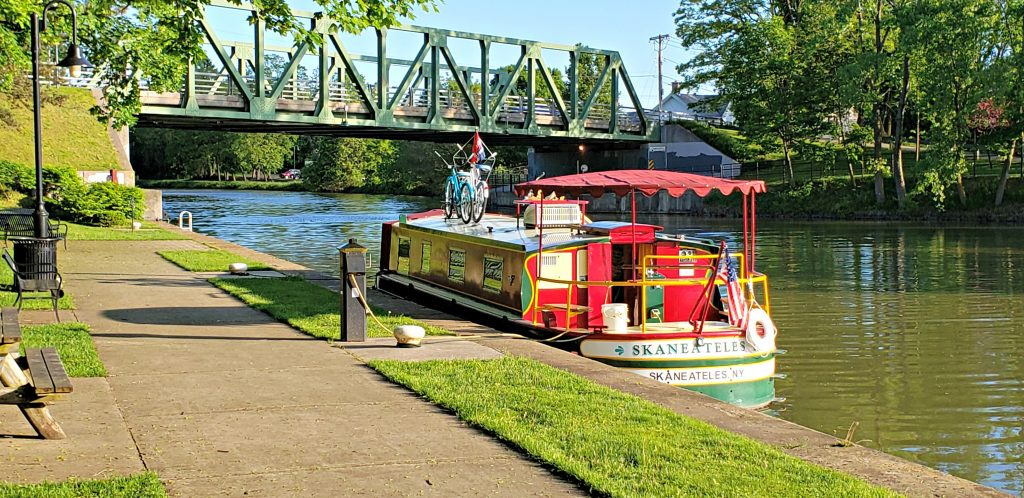 Red and green packet boat tied at pier on Erie Canal while a warren through truss bridge runs overhead.