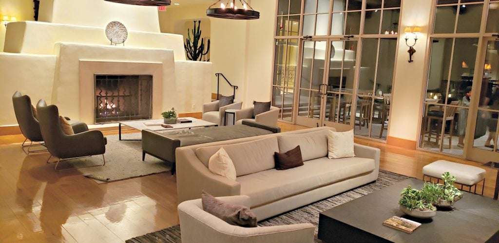 Living room-style lobby area with huge white fireplace, light-colored furnishing and sleek, modern lines. Best place to visit 2020.