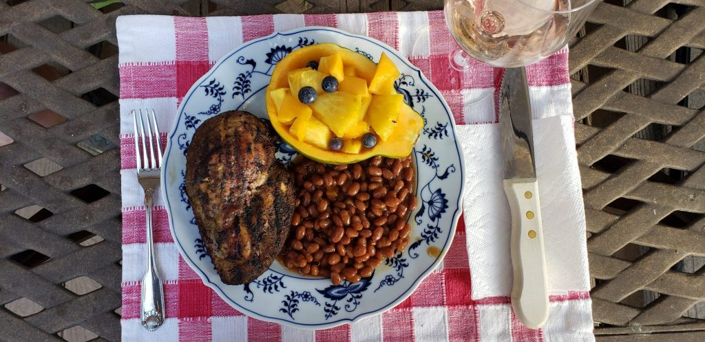 Plate of smoked chicken breast, brown beans and half a papaya filled with pineapple chunks, blueberries and chunked papaya