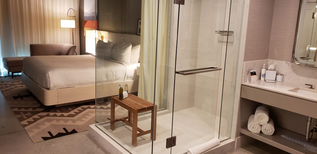 Stand alone glass shower has teak bench - can see king-sized bed through the glass enclosure