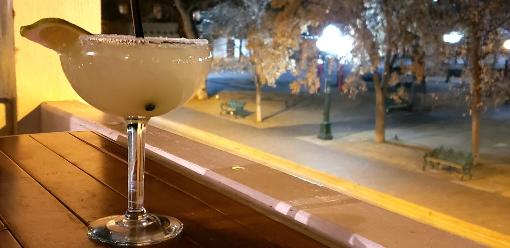 One of the best Margarita in Santa Fe sits on a small bar table that overlooks the Santa Fe plaza at night. Old fashioned gaslight-like globes illuminate park benches below
