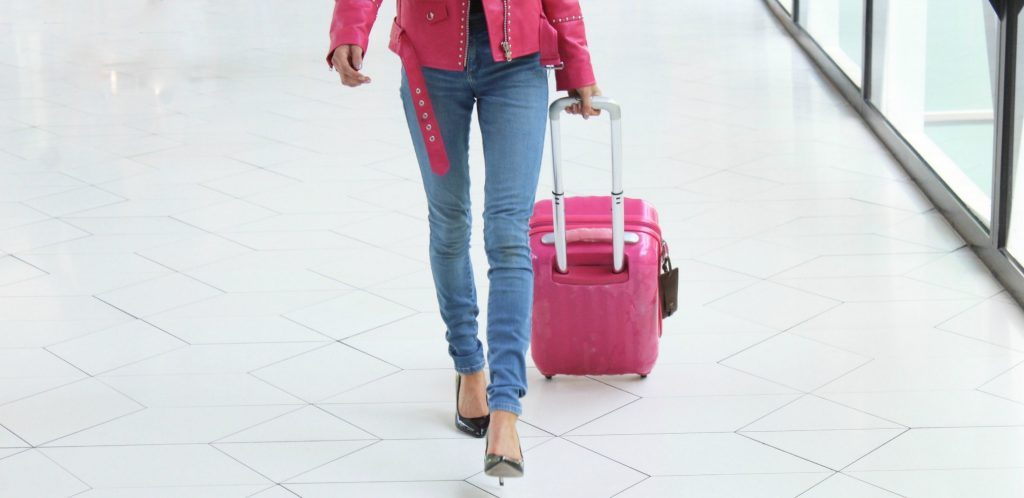 Woman in pink leather motorcycle jacket pulls pink carry on bag that rolls on white airport floor - Best Carry On Luggage for Women