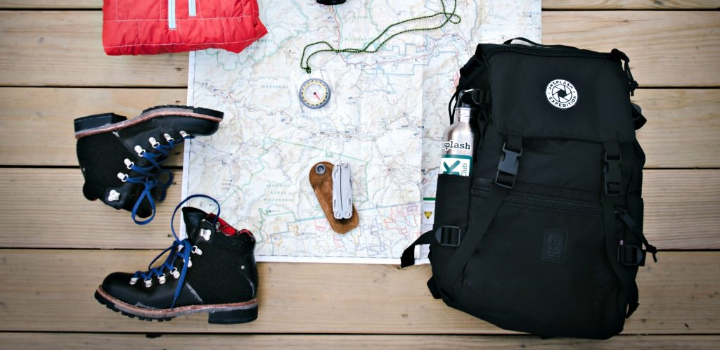 still life with black backpack, black boots laid out on map with compass shows Best Backpack for Air Travel
