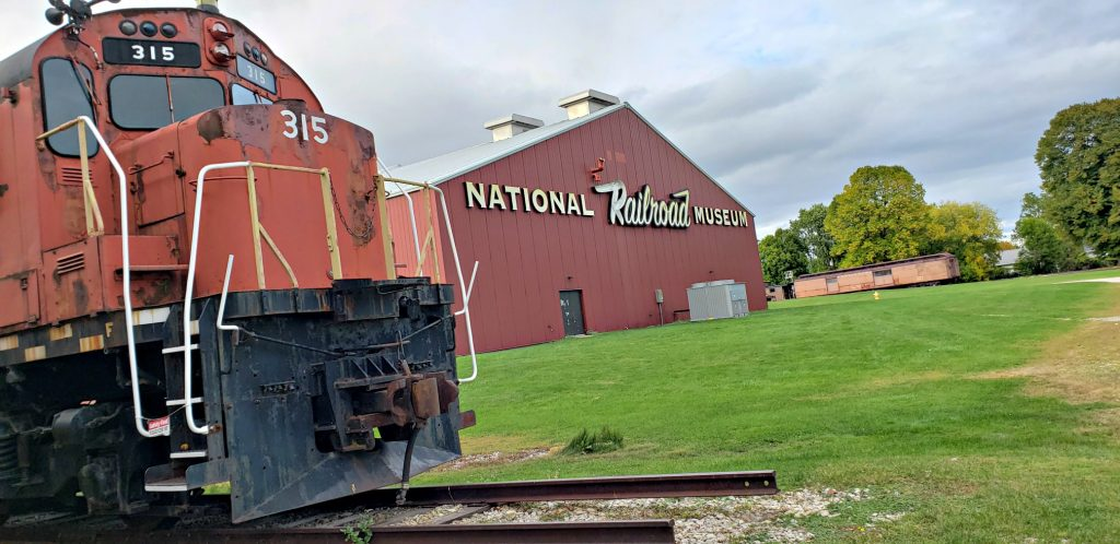 "red locomotive in the foreground, train barn in background with sign reading ""NAtional Trailroad Museum,"" which is One of the Best Green Bay WI Attractions"