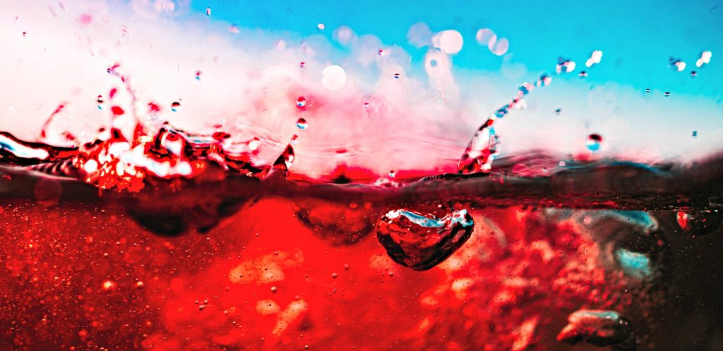 image of close up of red wine showing air being mixed in near rim of glass -depicting just what does a wine aerator do