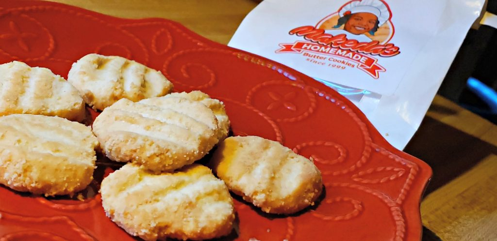 small sugar cookies sit on re plate with bag behind that read Makeda's Cookies - yummy food Memphis TN