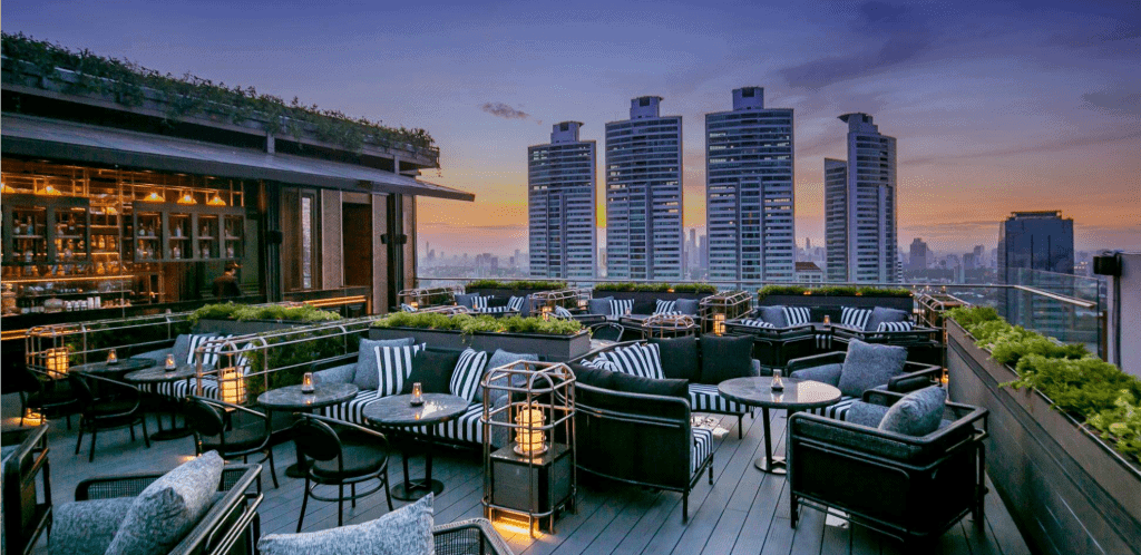 smallish patio bar on the rooftop of Bangkok-outdoor comfy chaise loungs and chairs with views of the highrise BAngkok behind making it a best rooftop bar in Bangkok