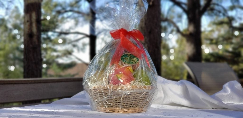 fruit gift basket wrapped in cellophane with red bow is exotic fruit gift basket
