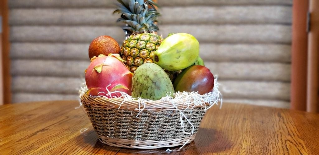 exotic fruit box arranged in woven basket sits in center of wooden table