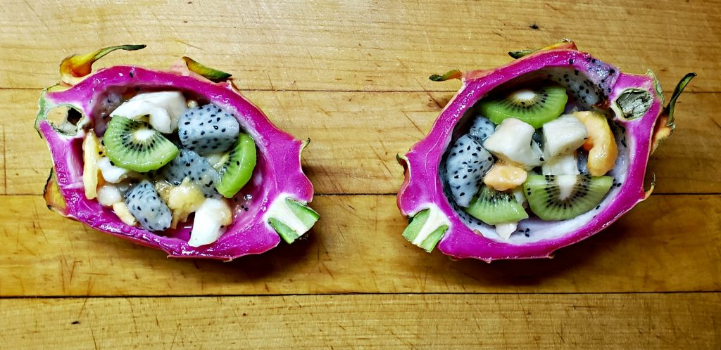 dragon fruit sliced in two, hollowed out and the fushia pink rind filled with cubes of white fruit, sliced green kiwi and chunks of pink papaya and cream-colored cherimoya