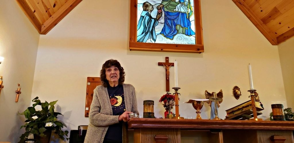84 year old woman stands at altar of one of the Catholic shrines in Wisconsin - stained glass window above and cross on wall