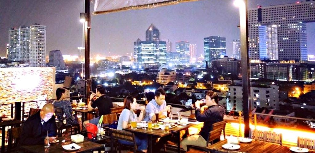 lOCALS AND TOURISTS SIT AT TABLES IN THE OPEN AIR WITH CITY PANORAMA IN THE BACKGROUND AT ONE OF THE BEST ROOFTOP BARS BANGKOK