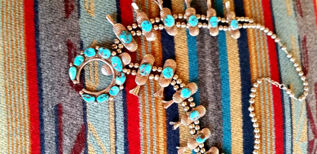 Large squash blossom necklace with snow white turquoise lays on colorful woven blanket is sample of Native jewelry one of the hings to see in Flagstaff