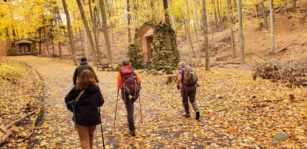 4 hikers stride up steep trail to next station of the cross at Holy Hill WI through the golden leaves