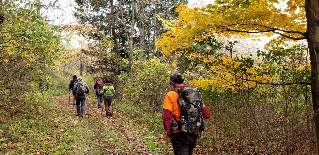 4 hikers spread out along the Ice Age Trail Holy Hill section under trees