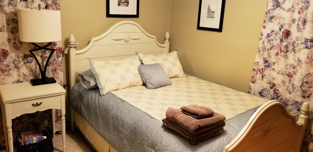 queen bed with lamp on white French provincial night stand - towels are stached on bed waiting to welcome the next guest to this Elkhart Lake lodging
