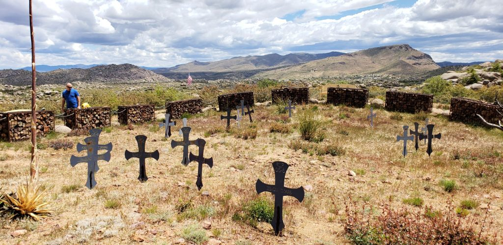 iron crosses in the dry desert box canyon with mountains on horizon