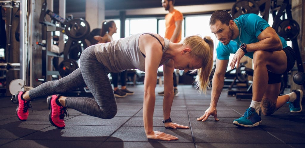 personal trainer with client in gym