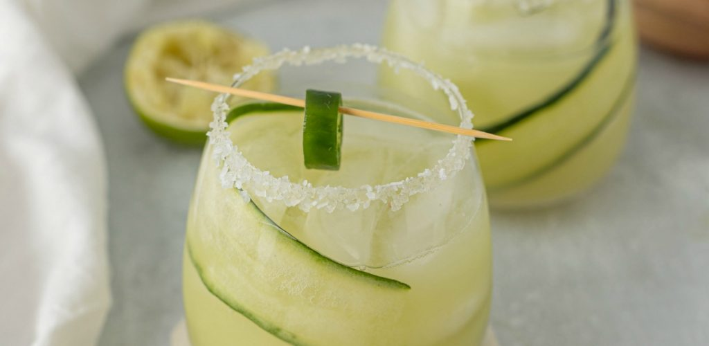 close up of rounded low glass with salted rim filled with margarita - tooth pick with jalapeno on it sits across top of glass
