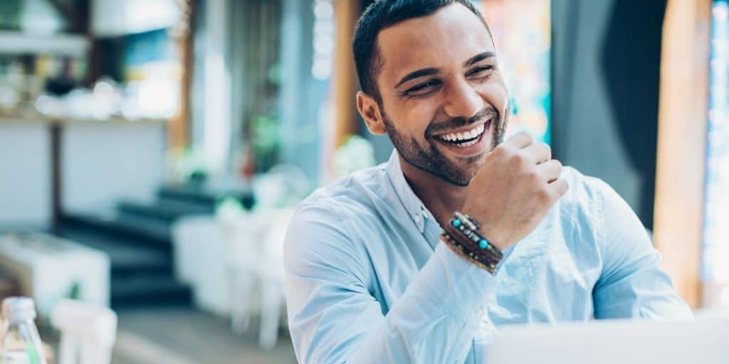A smiling man mastering these life-changing positive habits