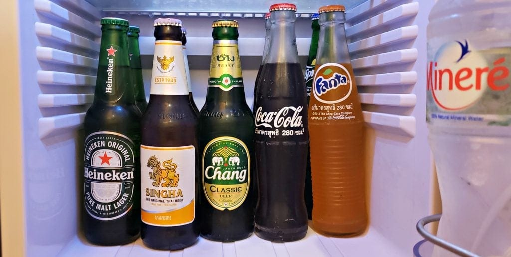 Inside of small refrigerator with Heineken, two local beers, a Thai Coke and Fanta all in glass bottles.
