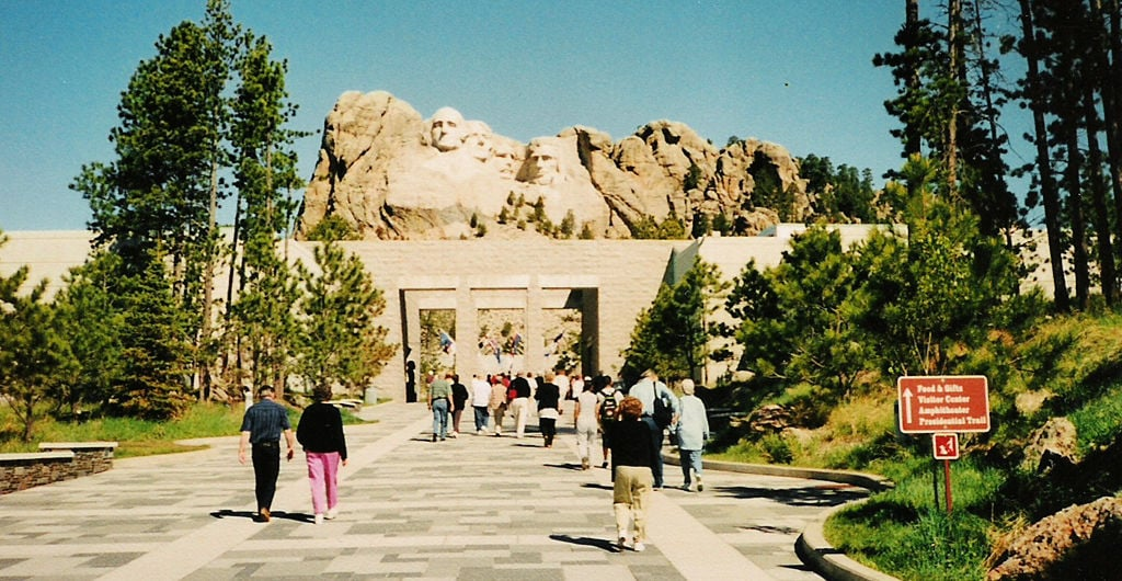 crowds of people enter the front gates of Mount Rushmore