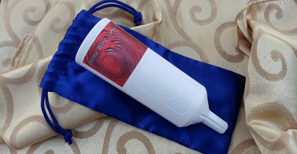 white cylindrical diffuser with smaller end lays on top of blue travel pouch