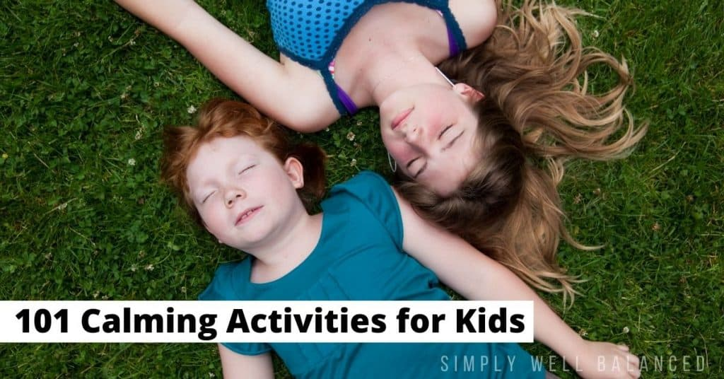 Calming activities for kids: Two girls relaxing in the grass with their eyes closed.