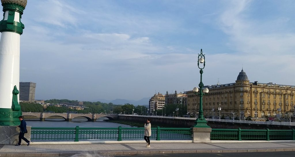 Pedestrians walk across San Sebastian bridge that connects the two parts of town. Wide blue river and arched bridge in background