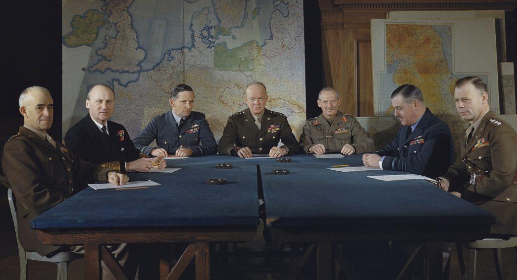 Seven commanders sit around war desk
