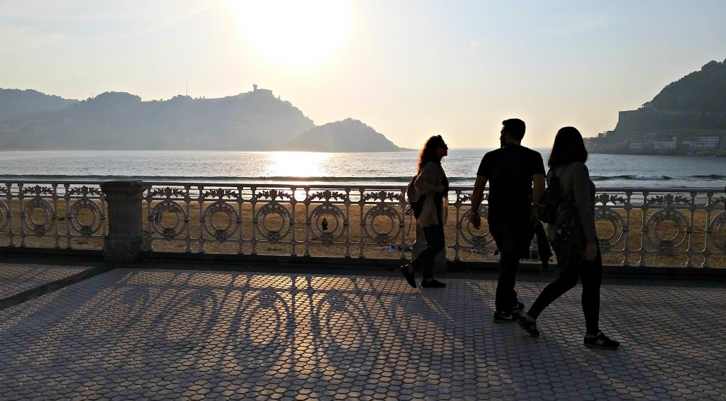 Three people walk siloutted against the sun setting over San Sebastian beach
